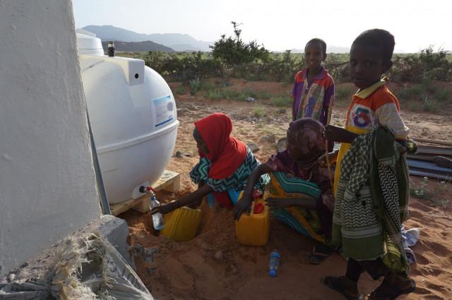 Trinkwasser für somalische Dorfbewohner und vorbeiziehende Nomaden
